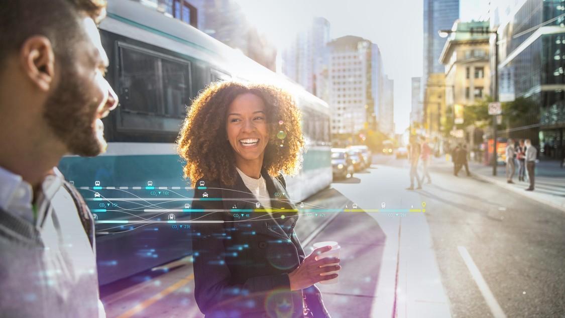 Eine Frau und ein Mann stehen lachend in einem urbanen Umfeld, im Hintergrund fährt eine Tram