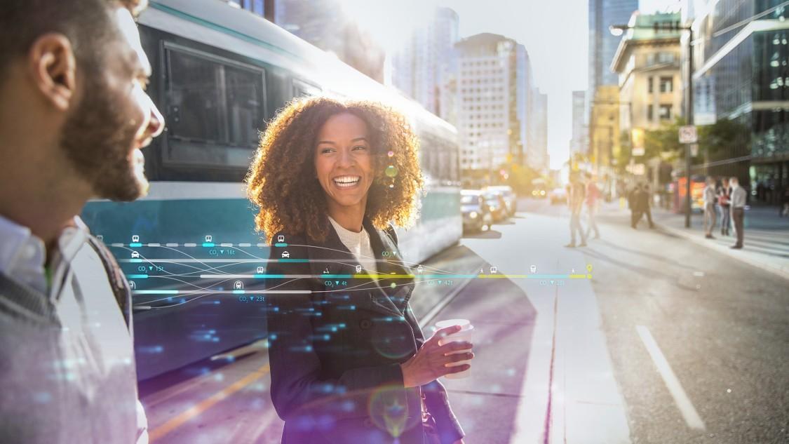 Zwei Personen überqueren lächelnd eine Straße in einer lebendigen, pulsierenden Stadt; hinter ihnen eine Straßenbahn; digitale Elemente über dem Bild zeigen die Möglichkeiten auf, die Smart-City-Lösungen für die Städteplanung bieten.