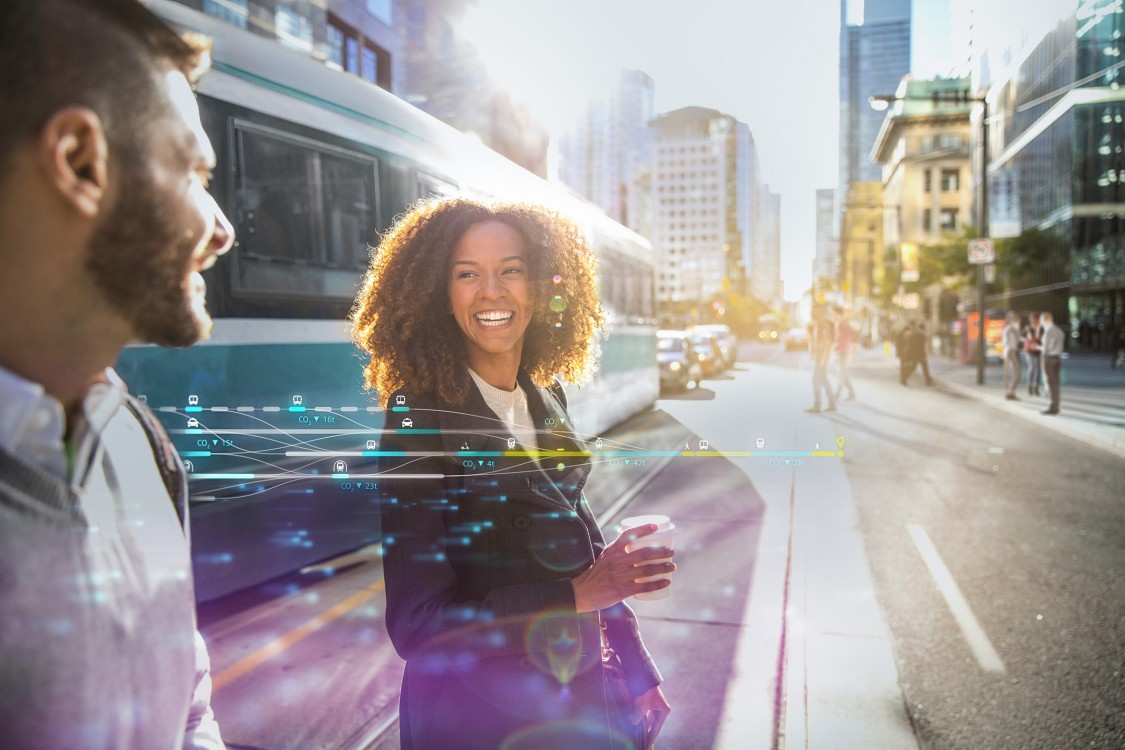 Two smiling people cross a street in a bright, vibrant city with a tram behind them; digital elements over the image display the possibilities offered by smart city solutions for urban transport.