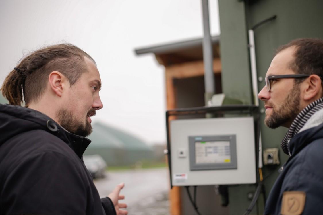 Daniel Schwier, Geschäftsführer SDS tec , unterhält sich mit weiterem Mann vor Outdoor Panel