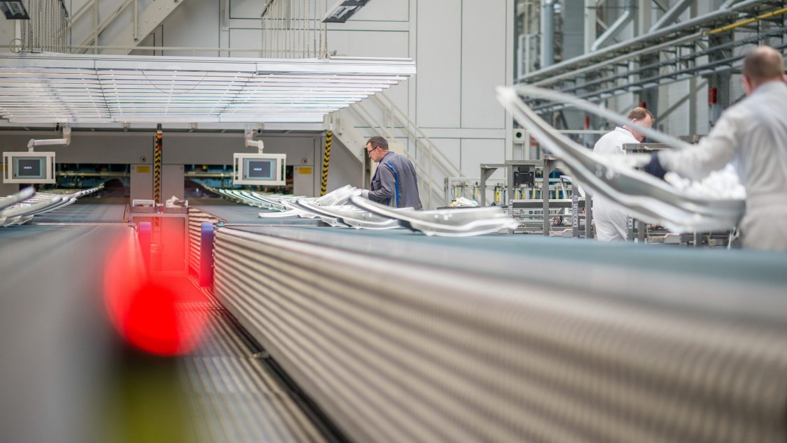 We look into the production of an automobile manufacturer: Several workers are visible in the left half of the picture. In focus: an object that is not exactly recognizable due to motion blur on a conveyor belt.