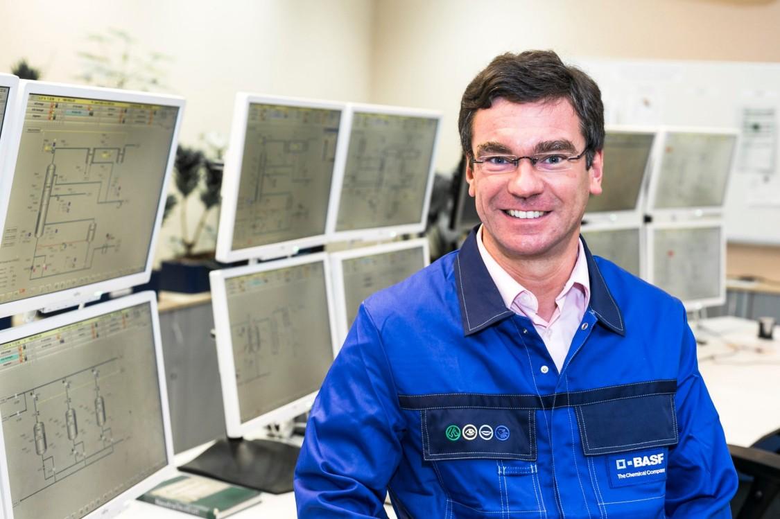 Das Bild zeigt einen Mitarbeiter von BASF am Standort Ludwigshafen in Deutschland. Er steht mit einem zufriedenen Lächeln in seiner Leitwarte.