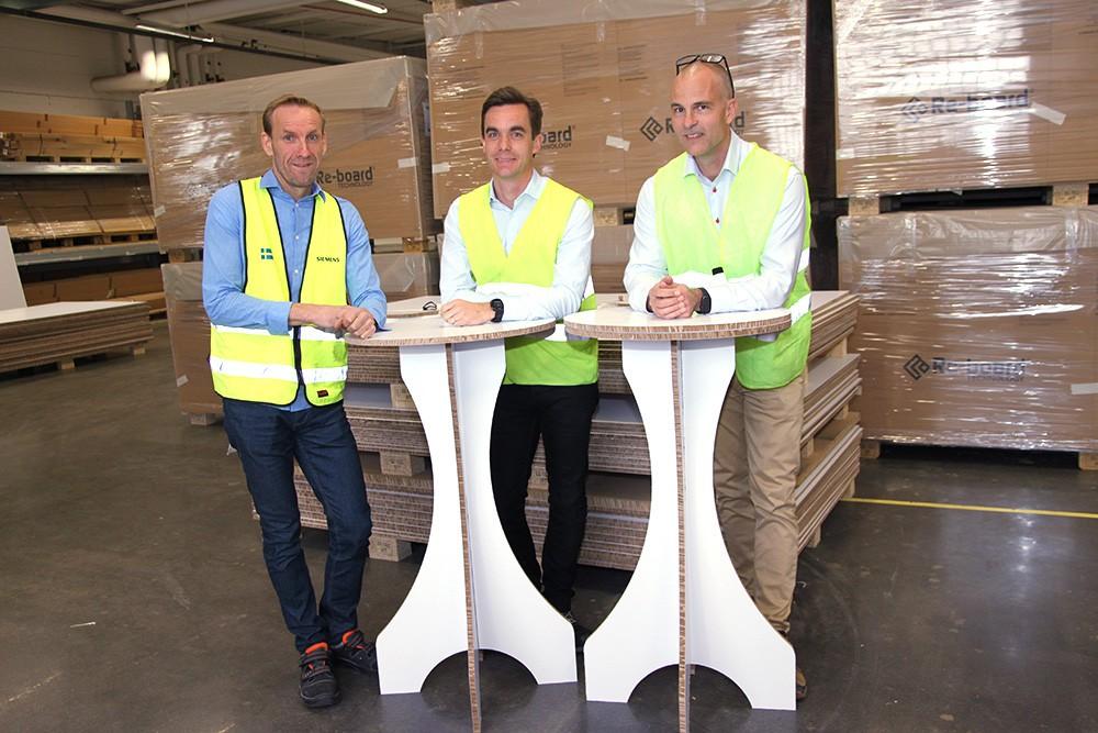 Re-board-skivan klarar såväl vassa som mjuka bockningar och produceras idag framförallt för utställnings- och exponeringsmateriel. 95 procent säljs till reklam- och mässföretag; 200 Re-board-partner runtom i världen jobbar mot olika designer och varumärken. Anders Roos är Account Manager på Siemens, Gustaf Redin är vd på Re-board Technology och John Södersten, då produktionschef på Re-board Technology, är den som har programmerat de båda processlinjerna – en blocklinje och en såg- och lamineringslinje. Papperet kreppas och skärs till 1,5x2 meter stora block som sågas och limmas. Två Simatic S7-1500T-cpu:er styr linjerna.