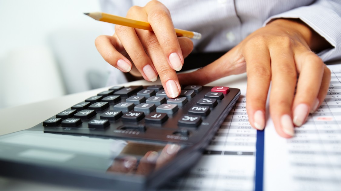 Lady with calculator checking hire purchase figures