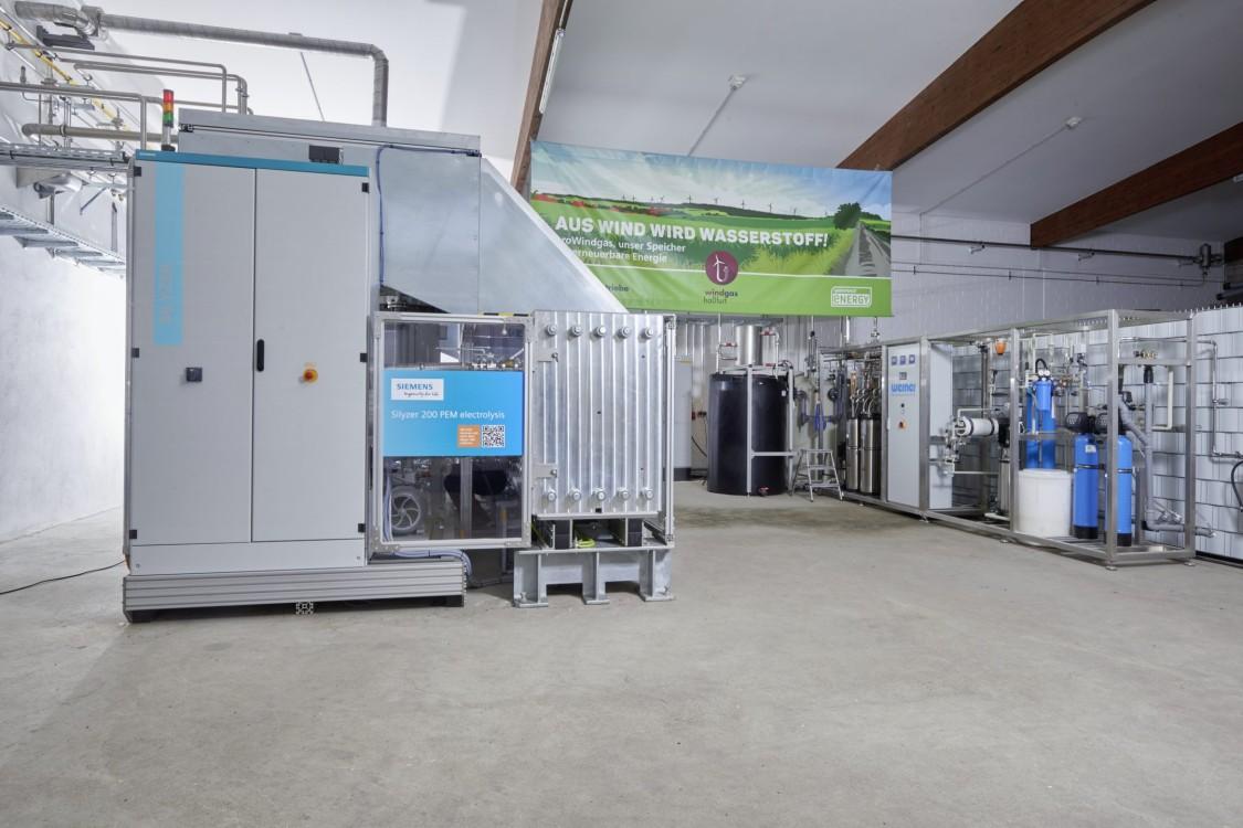 Blick in eine Fabrikhalle, in der grüner Strom und Wasser über einen Elektrolyseprozess in Wasserstoff und Sauerstoff umgewandelt werden.