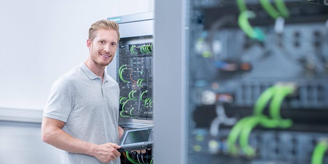 Pracovník manipulující s centrálním řídicím panelem Siemens pro průmyslovou komunikaci podniku