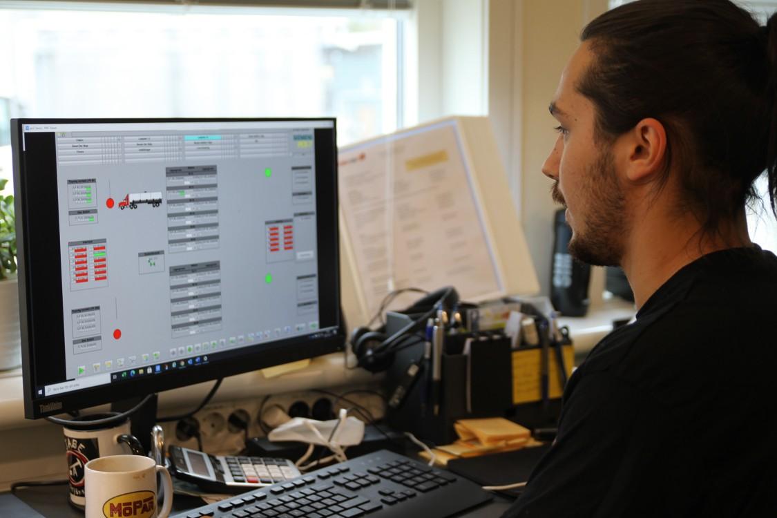 I driftrummet kan OKQ8:s drifttekniker, här Adrian Stenberg, enkelt felsöka och se diagnostik från givare, ventiler och pumpar i realtid. Lösningen är baserad på en standardiserad och integrerad systemplattform med Simatic PCS 7, Comos, Simit och Opcenter Execution och inkluderar recepthantering, modulär uppbyggnad för framtida förändringar, tydlig larmhantering, smidig åtkomst till data via rapporter samt full kontroll på flöden och lastade produkter.