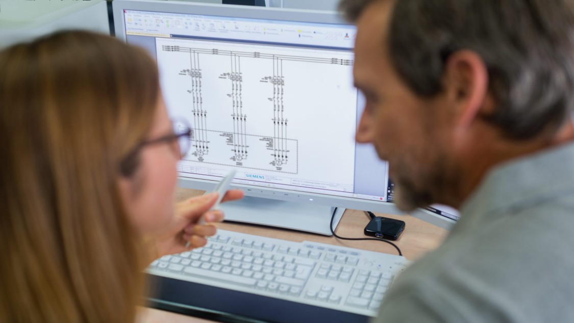 Zwei Ingenieure sehen sich CAx-Daten am Bildschirm an