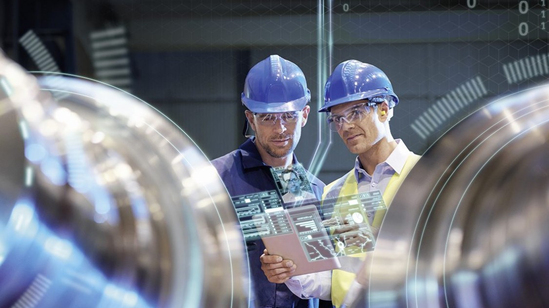 Two factory workers assessing drive train analytics. (Power utility)