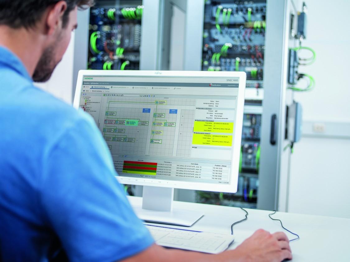 Blick über die Schulter eines Anwenders am Computer mit Blick auf die Oberfläche von SINEC NMS, im Hintergrund sind Schaltschränke mit SCALANCE und RUGGEDCOM Netzwerkgeräten zu sehen.