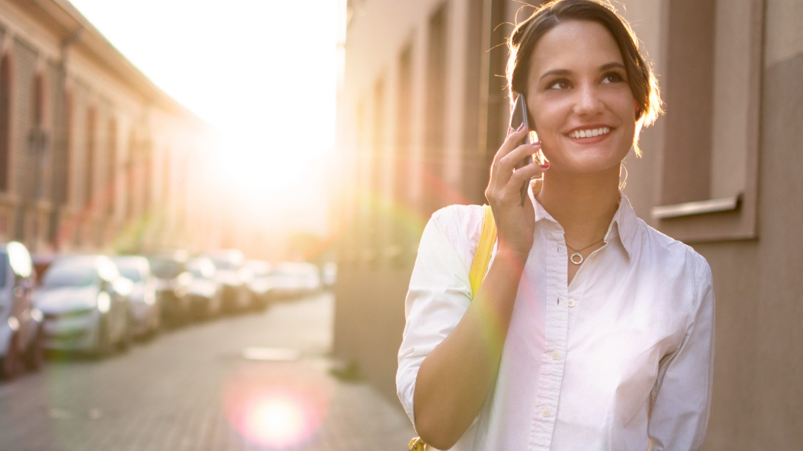Eine junge Frau steht neben einer Straße mit urbanem Charakter und telefoniert mit ihrem Smartphone
