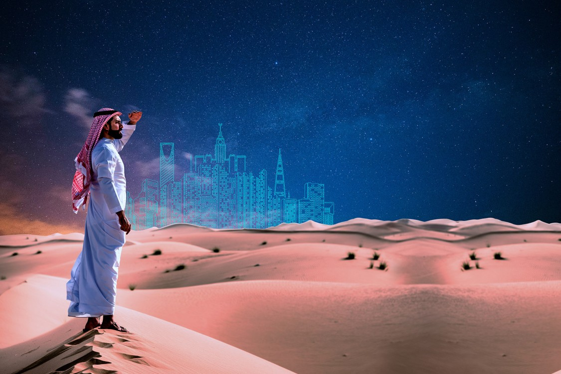 Saudi man standing on a dune, watching the horizon.