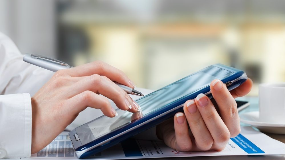 lady holding a tablet looking at finance lease options