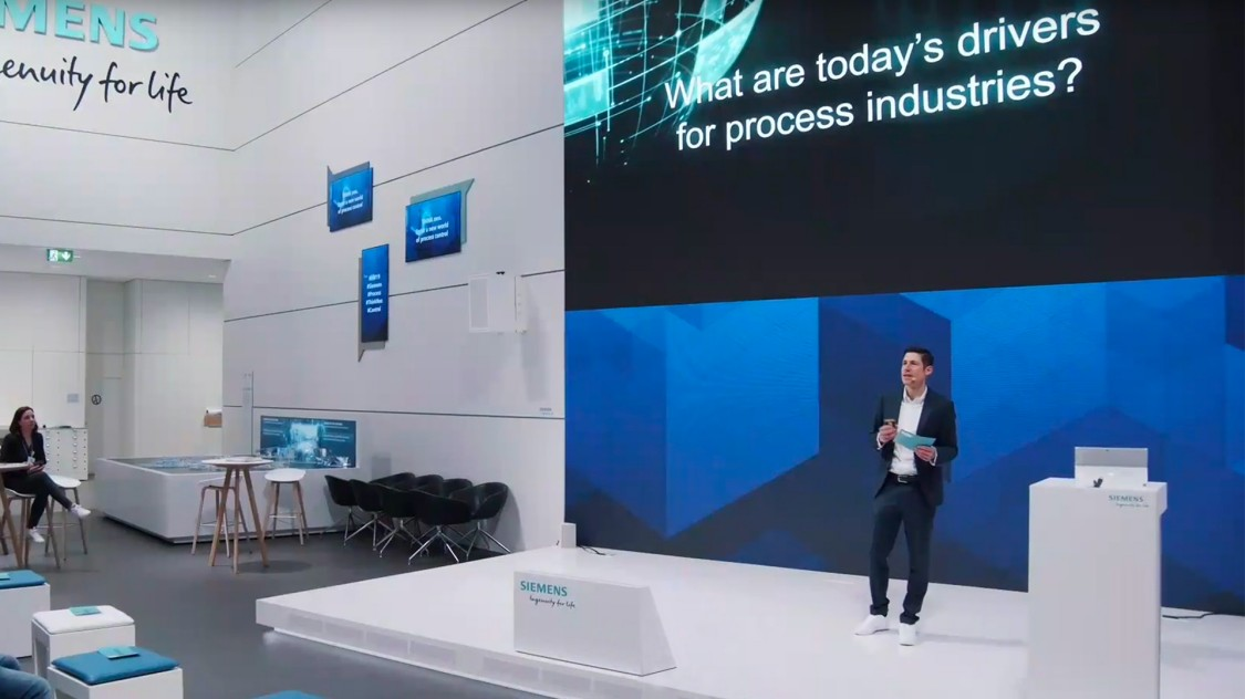 We see Manuel Keldenich standing on stage at the Siemens Hannover Messe exhibition.