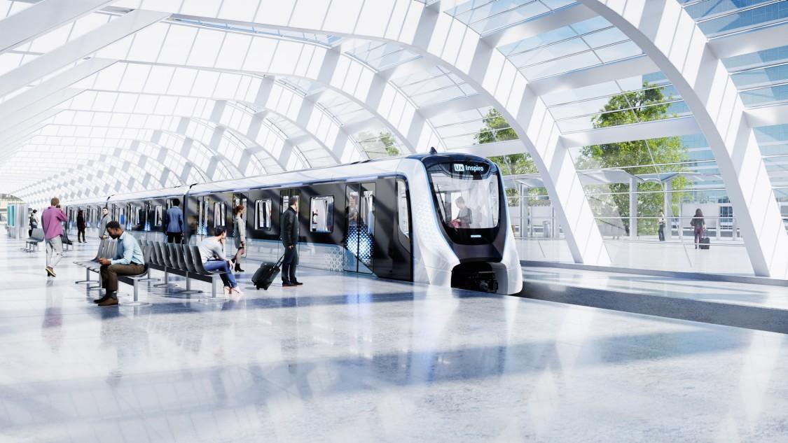 Ein Inspiro Metro Zug von Siemens Mobility hält an einem modernen Metro-Bahnhof. Am Bahnsteig sind Passagiere zu sehen.