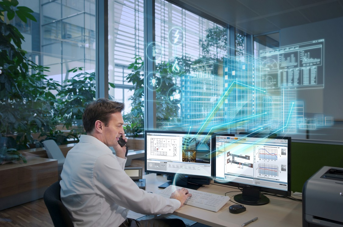 Business person at an office working in front of two monitors and a digital overlay