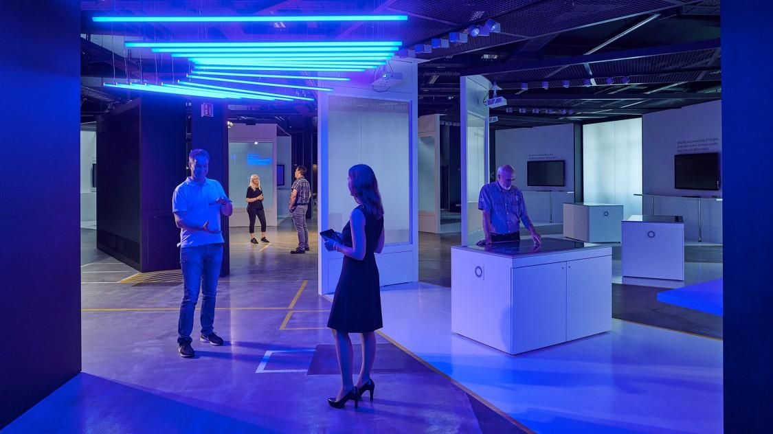 Blick in die Arena der Digitalisierung, ausgeleuchtet durch blaue Neonröhren an der Decke. Wir sehen Menschen, die sich unterhalten und die Umgebung erkunden.