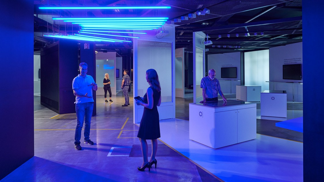 View into the arena of digitalization, illuminated by blue neon tubes on the ceiling. We see people, who are chatting and exploring the environment.