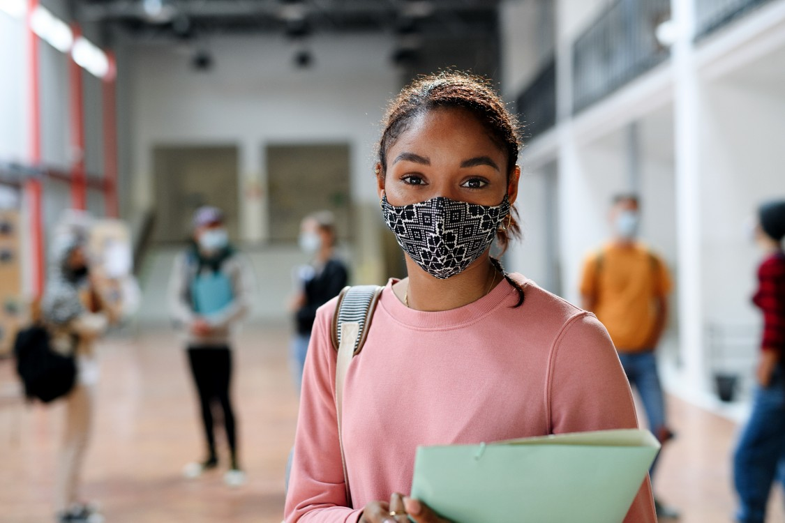 Re-open education - K12 young girl in school hallway with friends social distancing during COVID pandemic and school reopening.