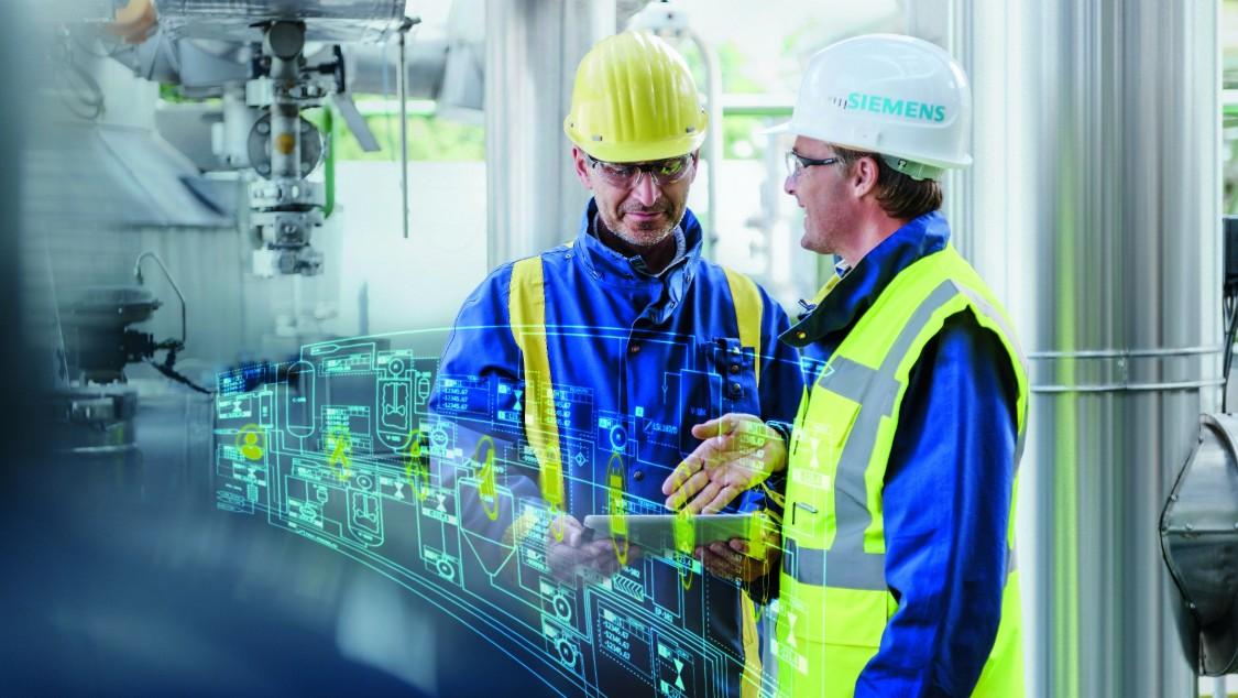 In einer Anlage der chemischen Industrie tauschen sich zwei Männer in Arbeitsbekleidung miteinander aus, in einer Hand ein mobiles Tablet-PC. Bestandteil des Bildes ist ein digitaler Layer, der einen typischen Prozessablauf in virtueller Form zeigt.