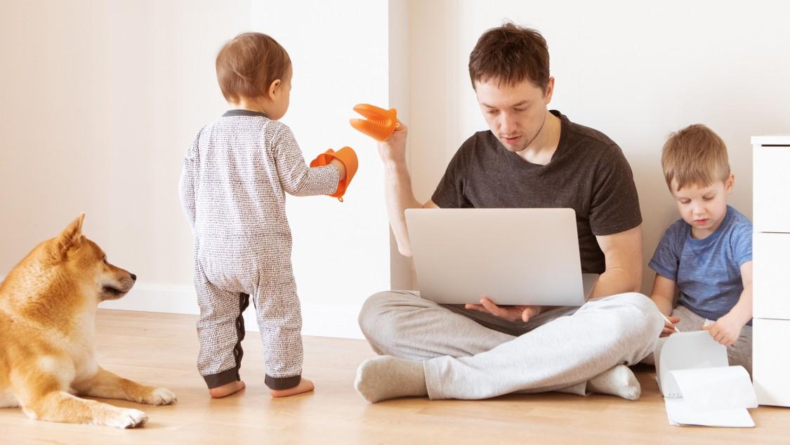 Man som arbetar hemifrån, som distraheras av två små barn