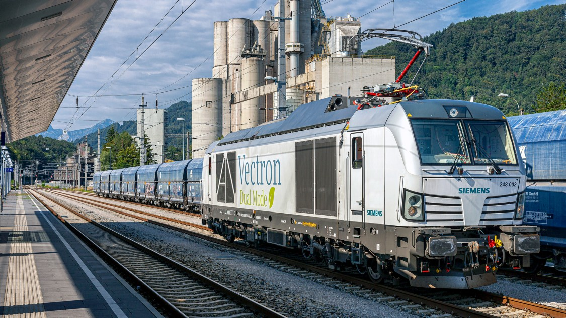 Picture of a Vectron Dual Mode locomotive with raised pantograph at a station.