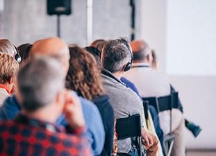 Das Bild zeigt Menschen bei einem Vortrag
