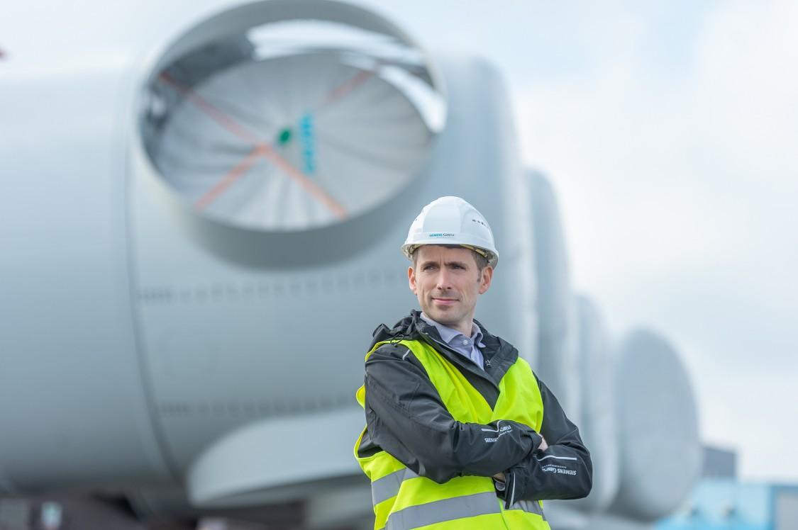 Arwyn Thomas steht mit verschränkten Armen vor einer Windturbine