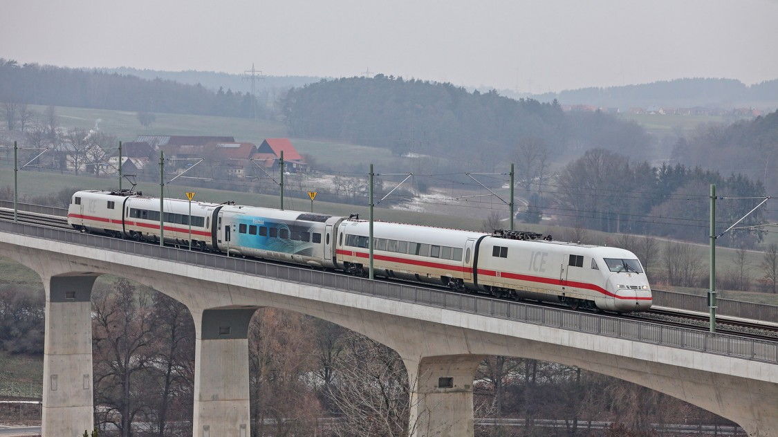 Test car of the Velaro Novo in operation coupled between existing train cars on a bridge