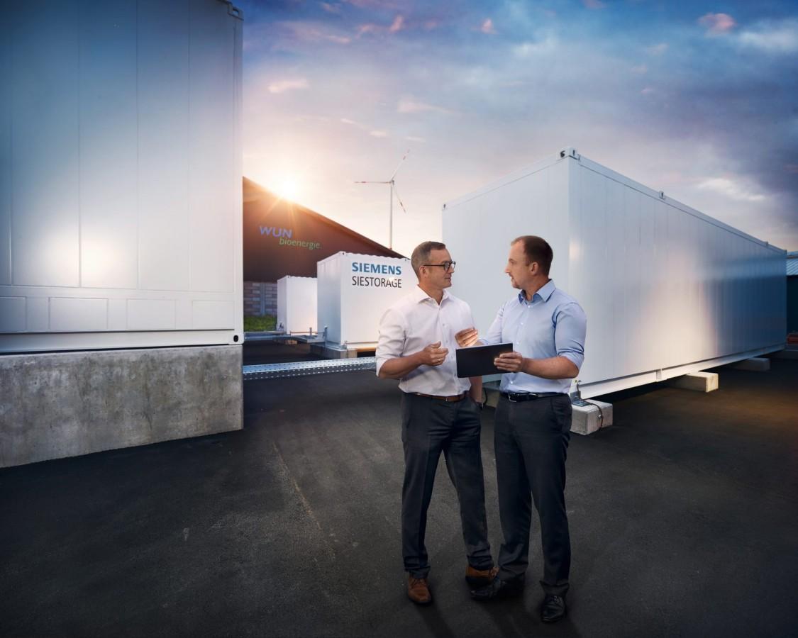 Wunsiedler Weg, zwei Männer stehen vor Batteriespeichern von Siemens