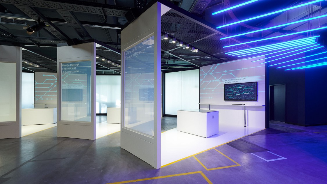 View into one of the seven theme rooms, the so-called challenge zones, of the Arena of Digitalization – illuminated by blue neon tubes on the ceiling.