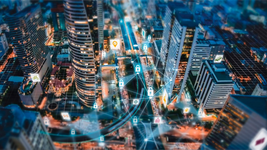 An aerial view of a city at night is overlaid with connected icons representing cybersecurity in mobility