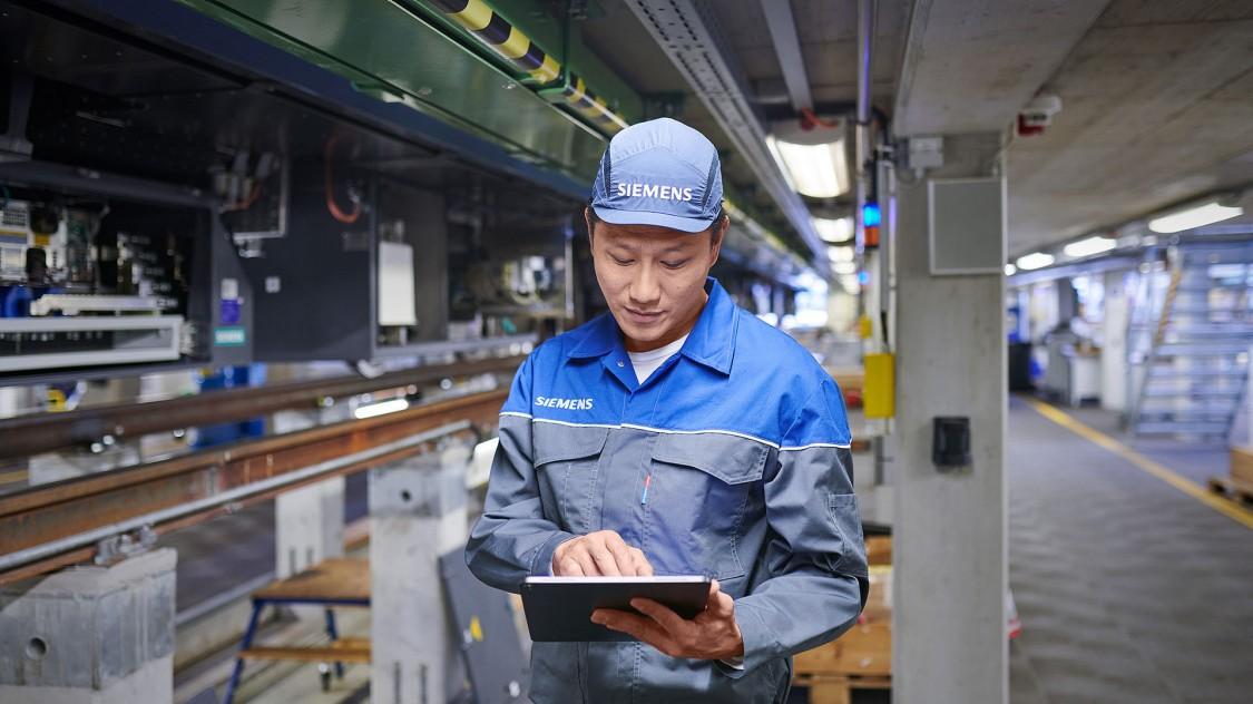 Ein Siemens Mobility Service-Mitarbeiter sieht auf sein Tablet während Service-Arbeiten an einer Metro in Bangkok durchführt.