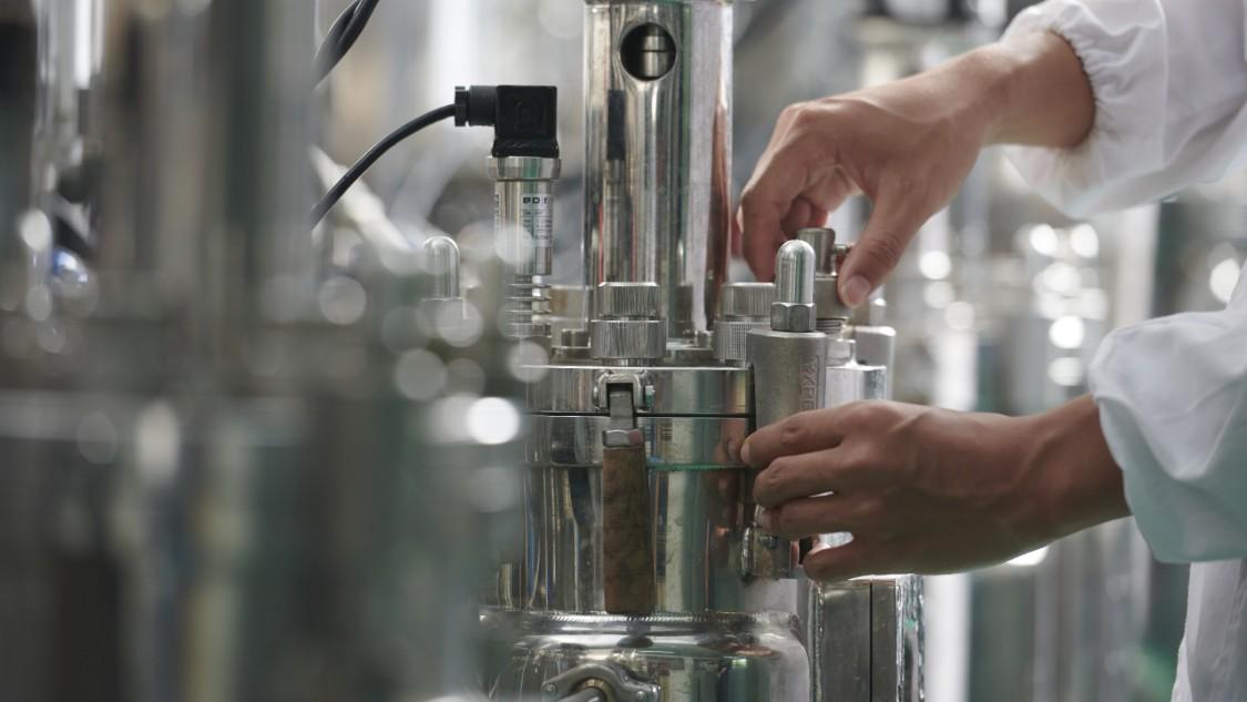 Blick in biochemisches Labor. Zu sehen sind die beiden Hände eines Laborarbeiters an einer Apparatur.