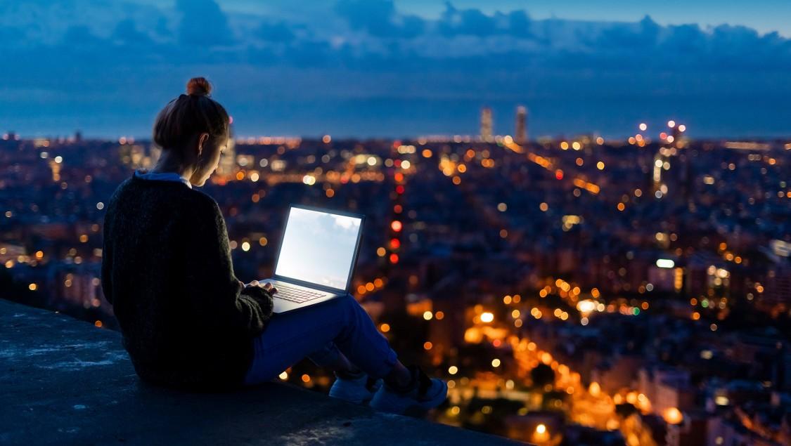 Frau, die nachts auf ihren Laptop und ihre Stadt schaut