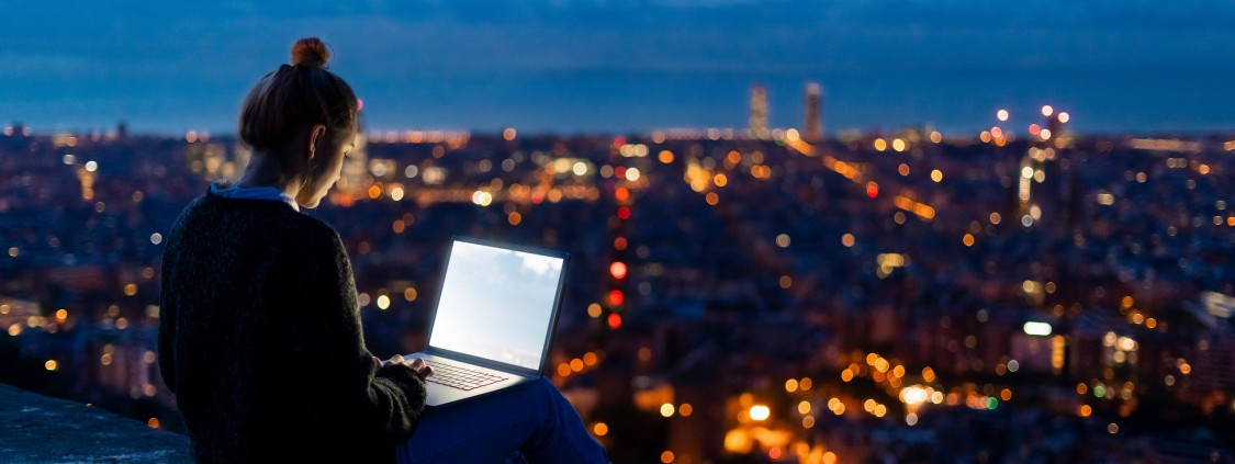 Woman working on a laptop in front of a city skyline.