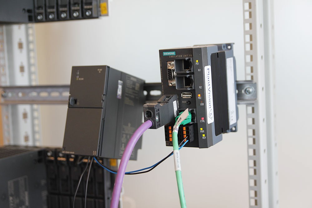 """Simit Unit är en smart modul som kopplas på fältbussen och låtsas vara utrustning (I/O-noder, frekvensomriktare, motorstartare m.m.) och """"lurar"""" styrsystemet att denna utrustning finns på plats. I detta fall används den riktiga cpu:n (s.k. Hardware-in-the-loop) och då kan man också felansätta hårdvara. Hur beter sig systemet om man rycker ett I/O-kort, hur ser det ut för operatören, blir det konstiga följdfel? Det går också att köra helt virtuellt med emulerad cpu istället för den riktiga (s.k. Software-in-the-loop)."""