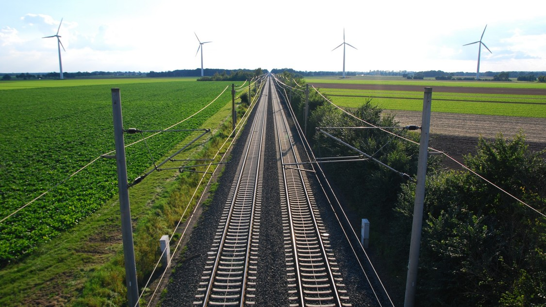 Two railtracks crossing rural landsape with wind tourbines in the horizont
