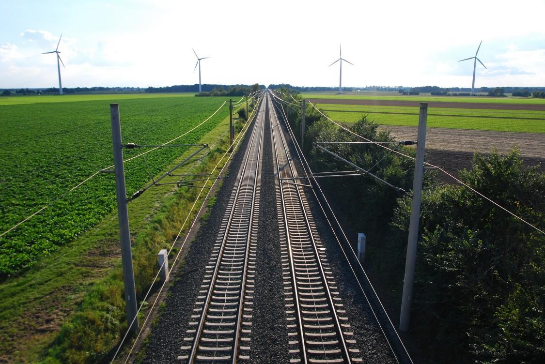 Gerade zweispurige Gleislinien vertikal durch eine ländliche grüne Landschaft