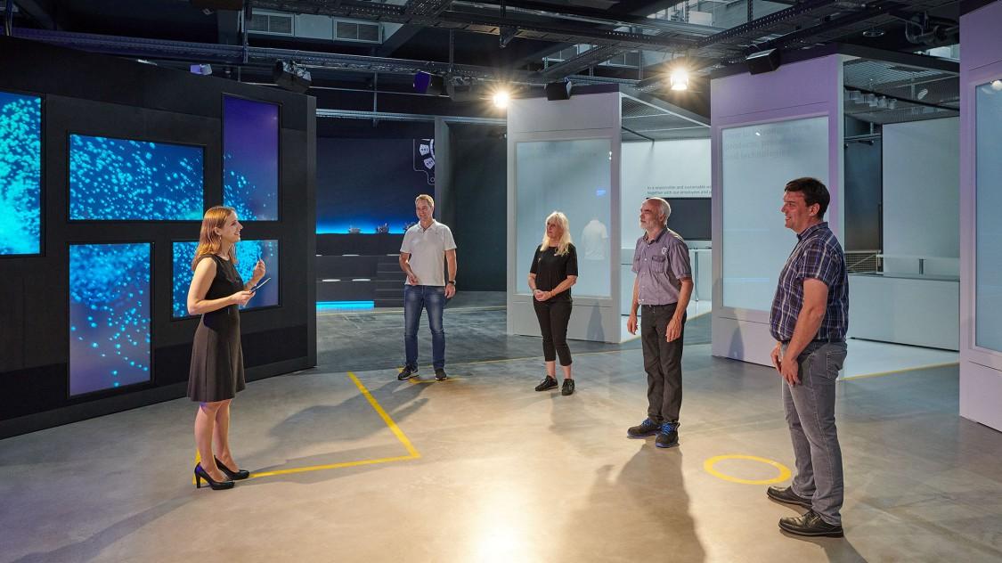 Arena der Digitalisierung mit einem weiblichen Guide, die einer kleinen Gruppe von Menschen vor einer Wand aus Bildschirmen und Raumteilern die digitale Transformation erklärt.
