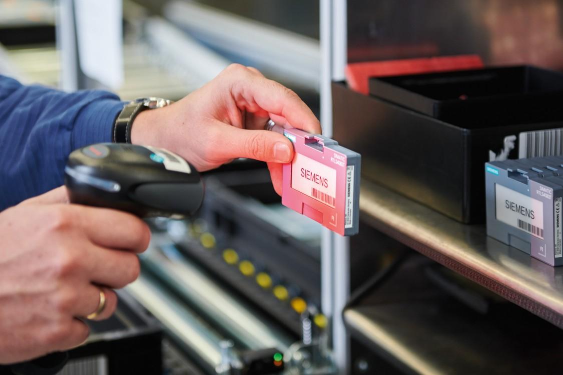 Ein Mann scannt das Display eines SIMATIC RTLS E-Paper Transponders