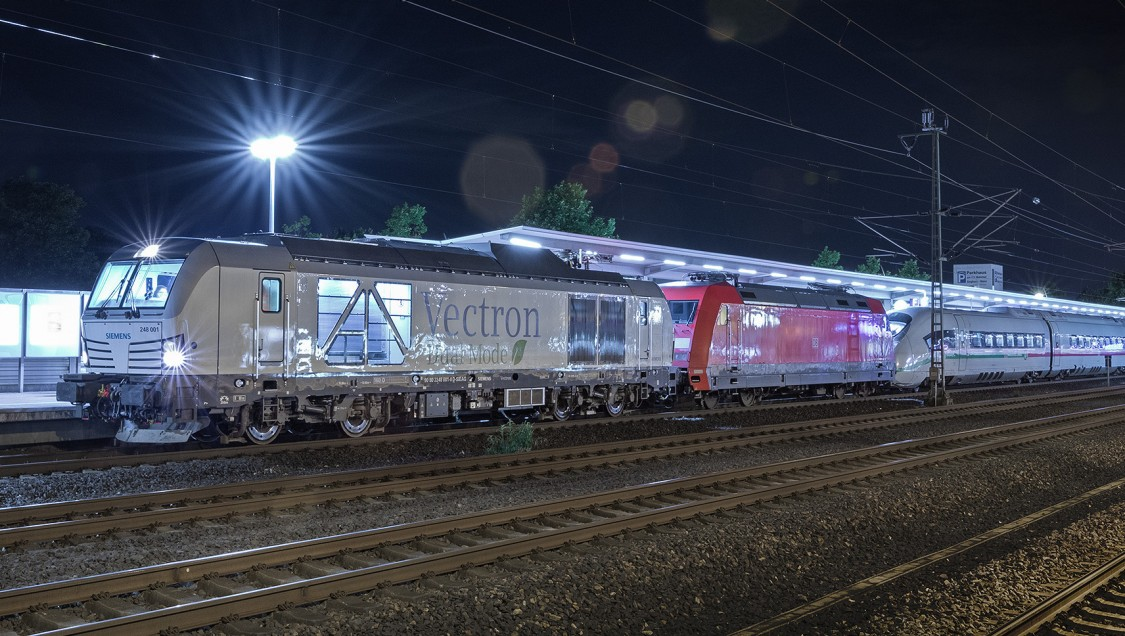 Bild eines Vectron Dual Mode am Bahnhof bei Nacht mit einem angehängten ICE Hochgeschwindigkeitszug.