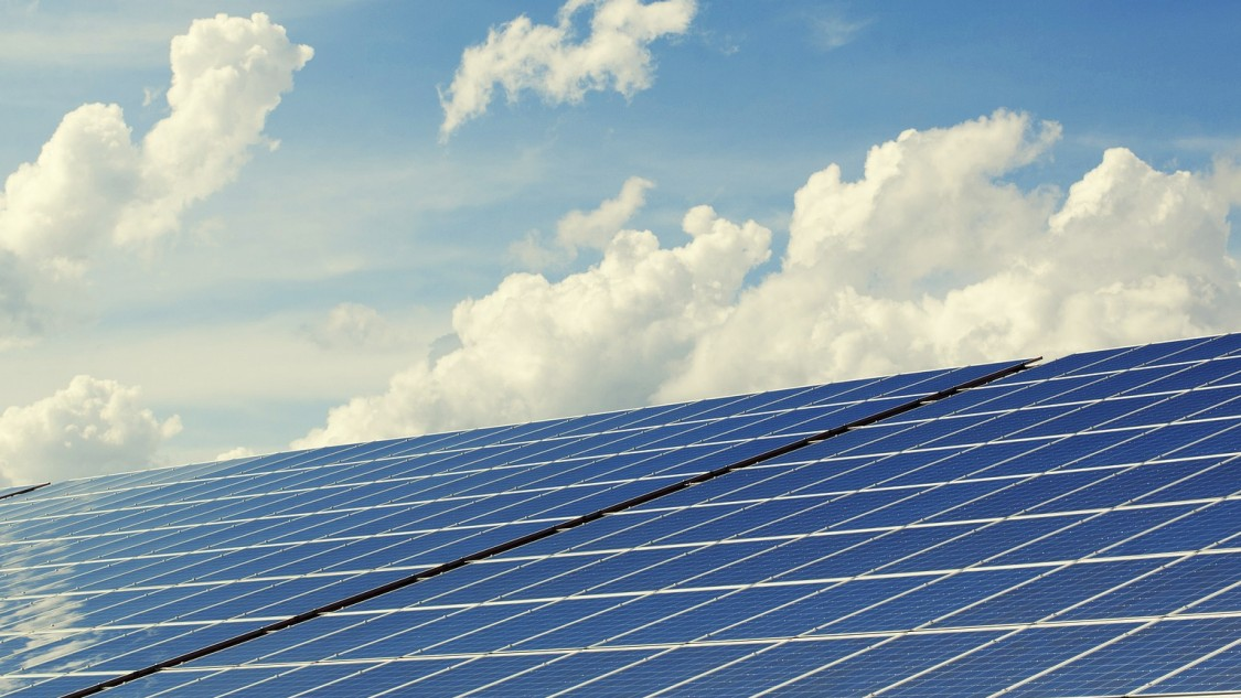 Image of solar panels against the sky and clouds background