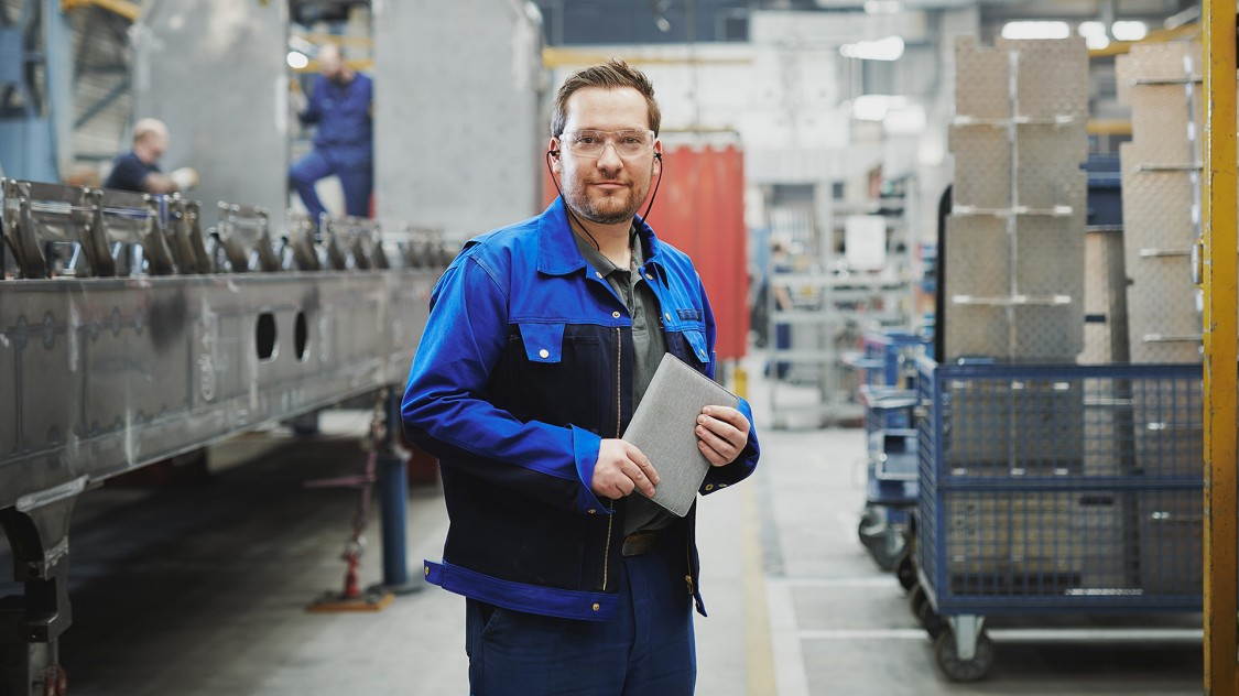 Gruppenleiter steht in Produktionshalle in München-Allach