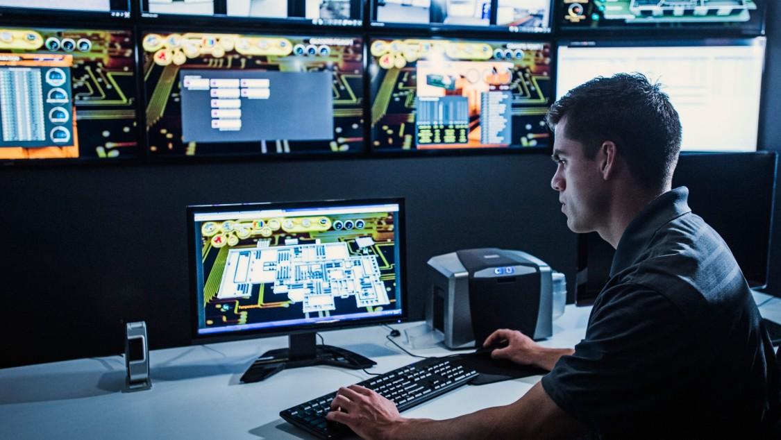 Mann in einem Kontrollraum überwacht sitzend einen Monitor auf seinem Schreibtisch, eine Monitorwand im Hintergrund.
