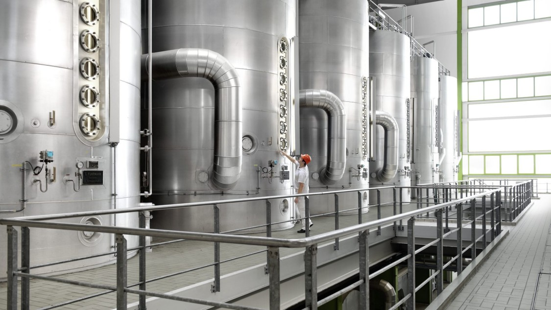View on a plant section with a few large tanks within a plant of the sugar industry. In front of one tank a man in working clothes is standing and checking the setting.