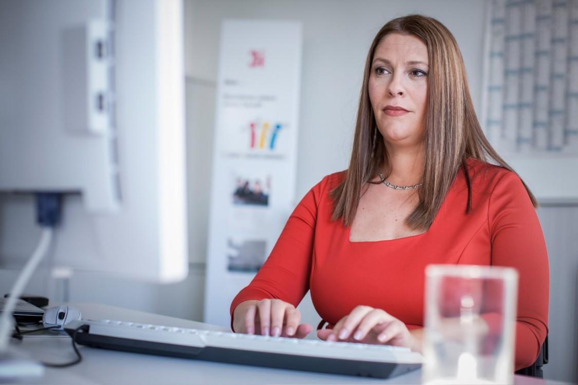 Marina sitzt am Schreibtisch und arbeitet an ihrem Computer