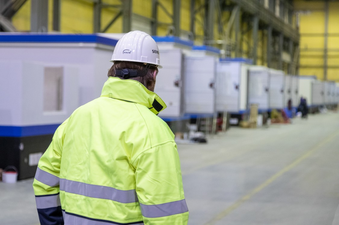 Picture of a technician in a yellow vest standing in a warehouse in front of a row of large gasoline tanks of the company ARAL