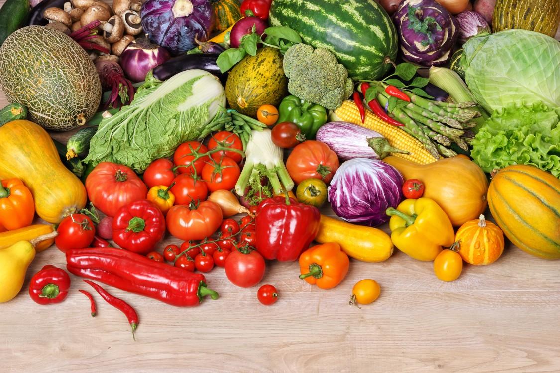 Em uma mesa de madeira estão espalhados diversos tipos de frutas, legumes e verduras