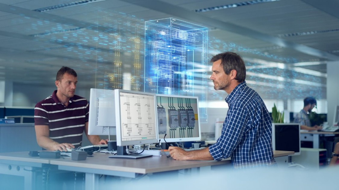 Two men on their computers working on control panel engineering